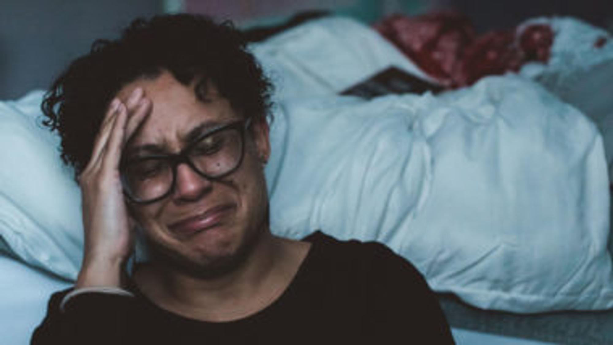 Frau weint vor einem Bett