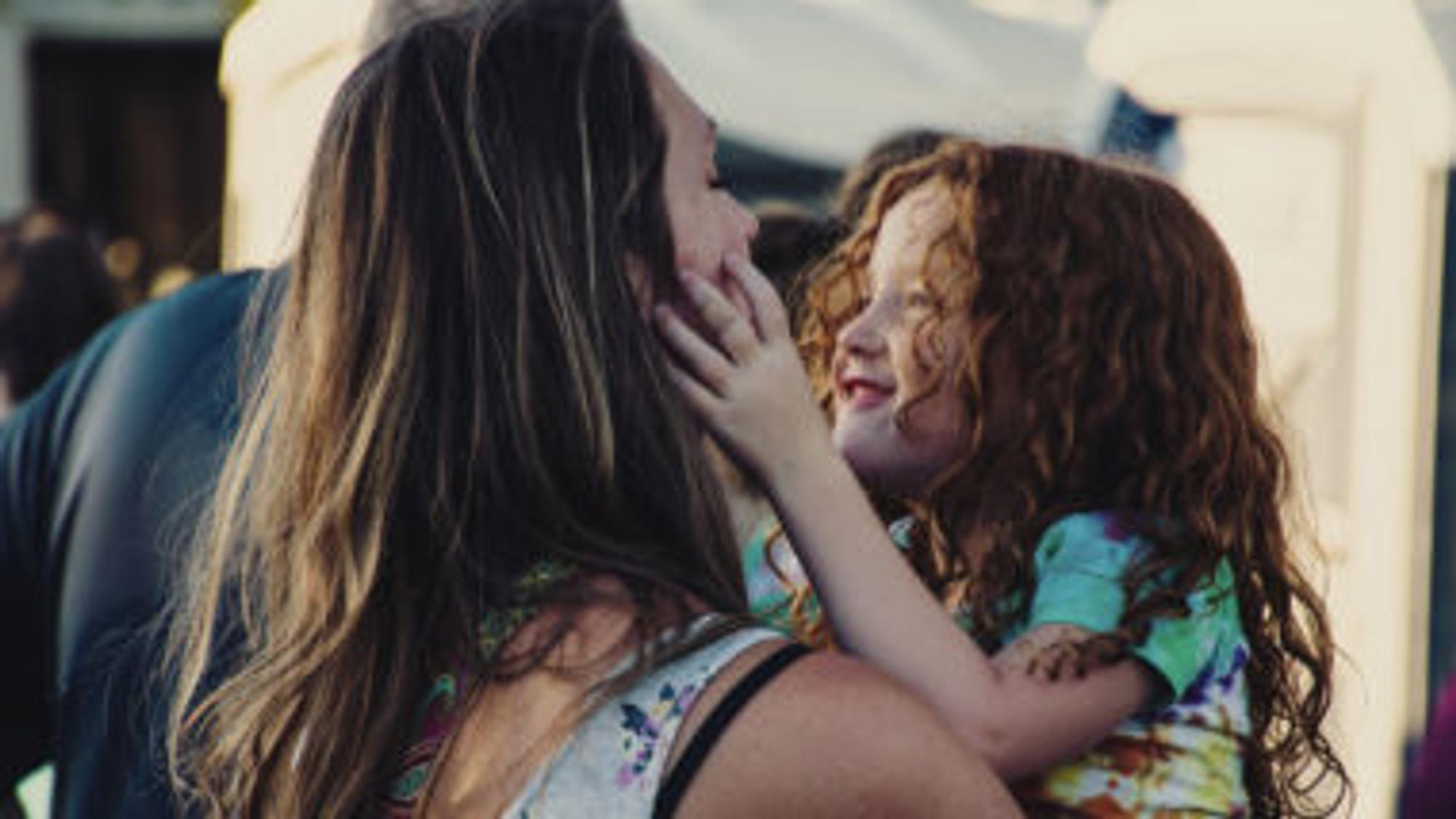 Mutter hat Tochter auf dem Arm
