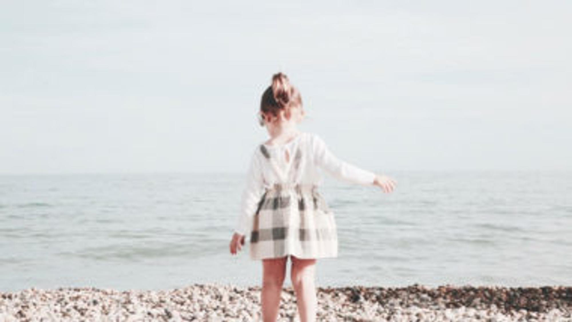 Mädchen läuft am Strand entlang