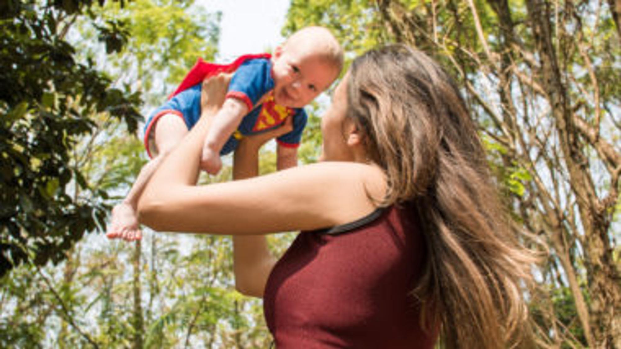 Mutter hebt ihr Kind im Superman-Strapler hoch