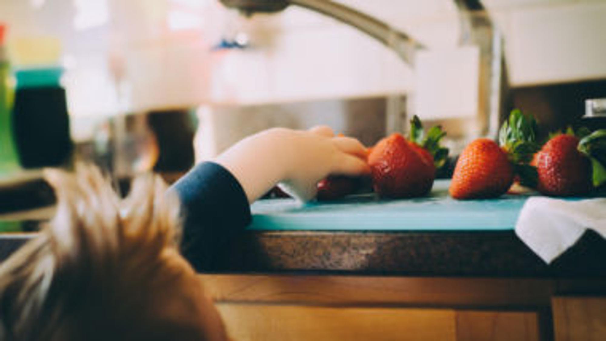 Kind, das nach Erdbeeren greift