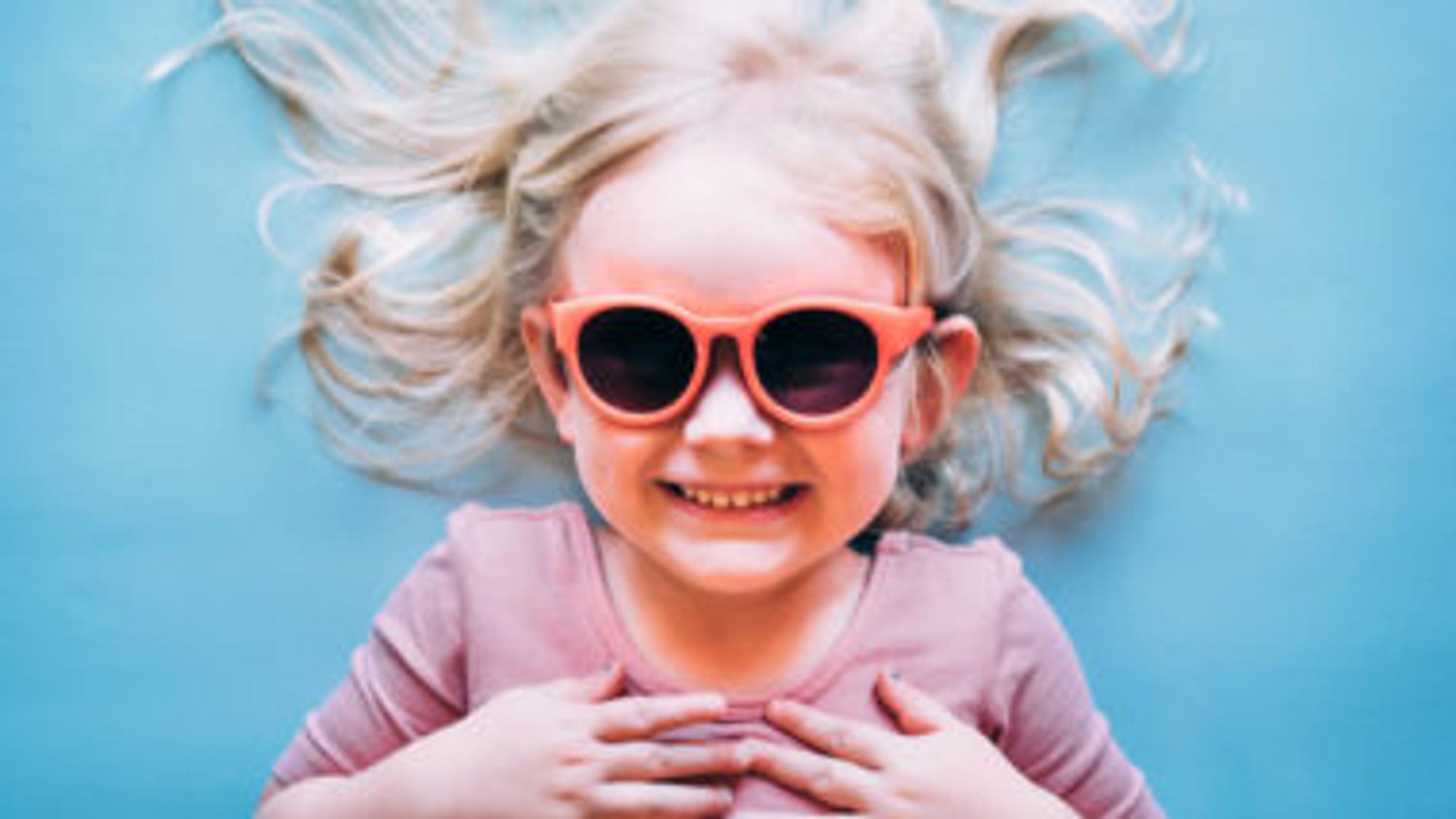 Blondes Mädchen mit Neon-Sonnenbrille