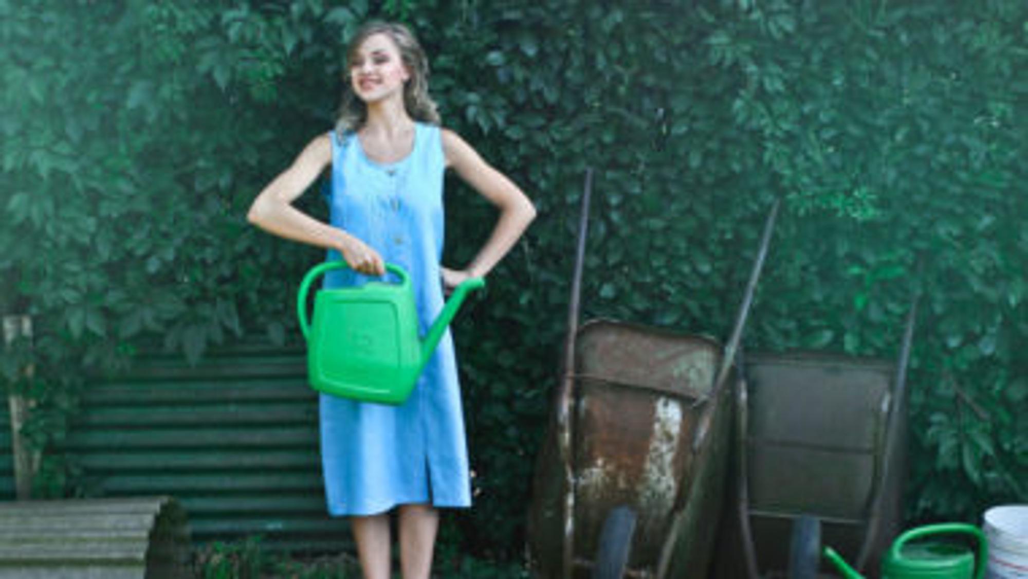 Frau steht im Garten und hält Gießkanne in der Hand