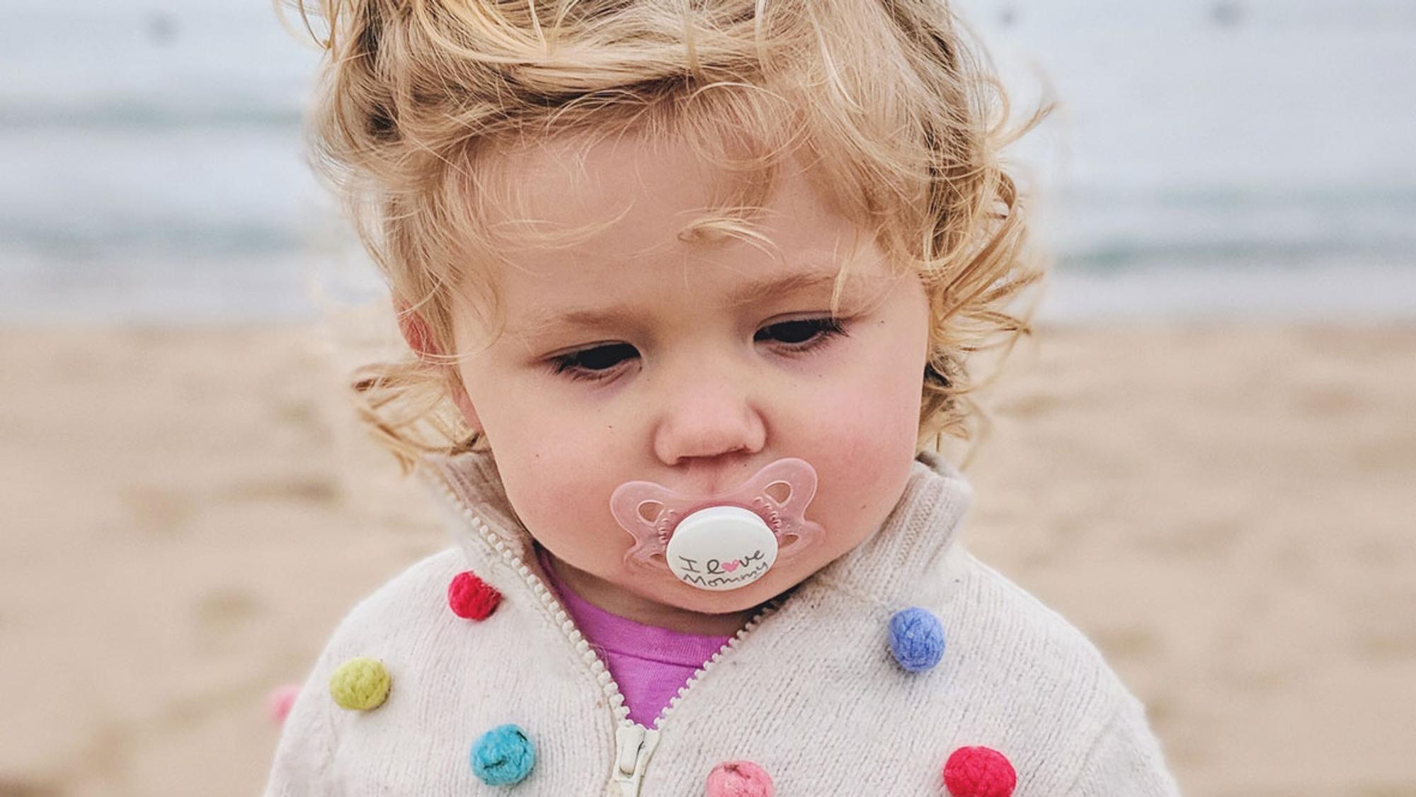 Blondes Kind mit Schnuller im Mund steht am Strand