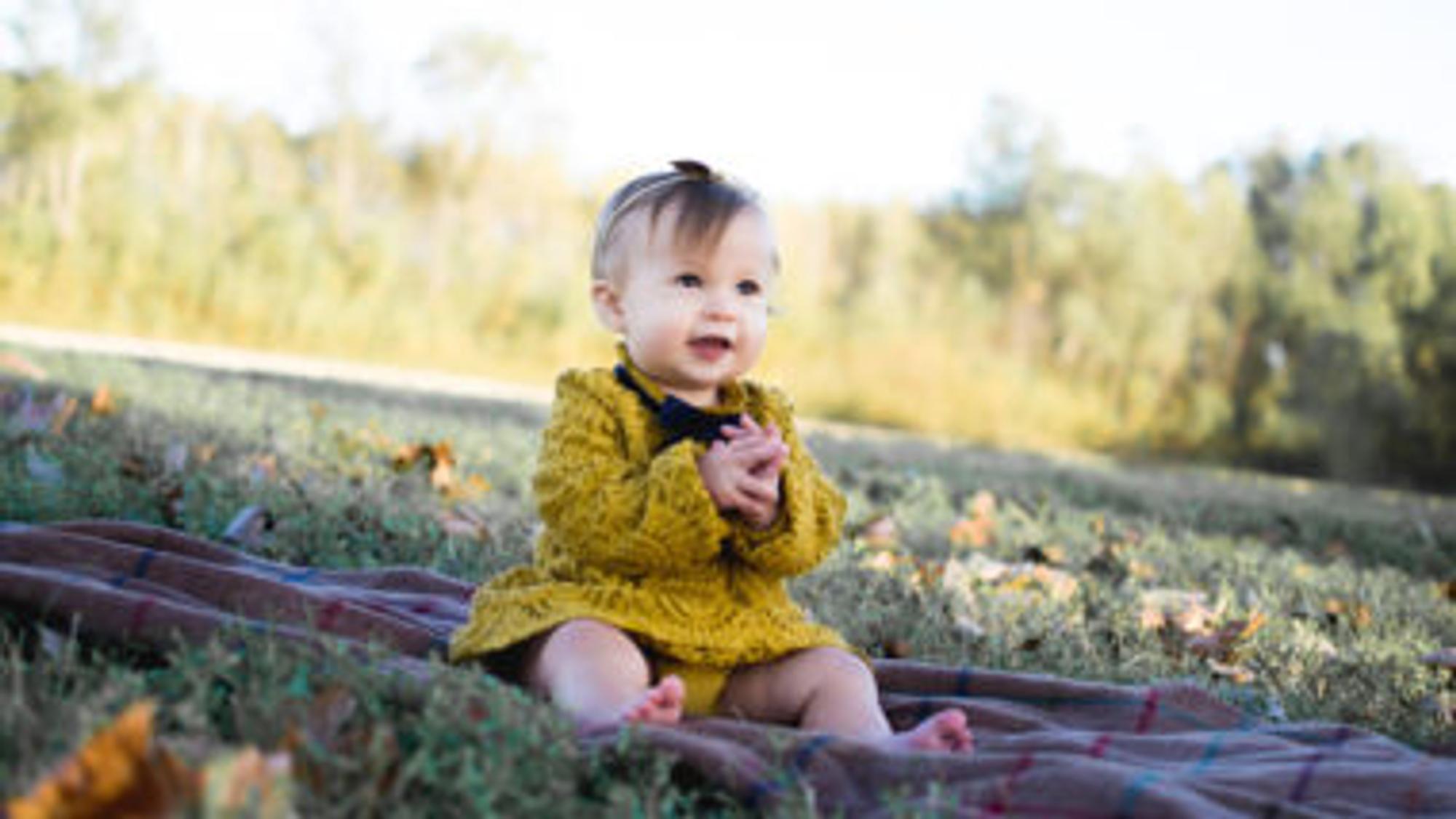 Baby in gelbem Kleid auf einer Wiese