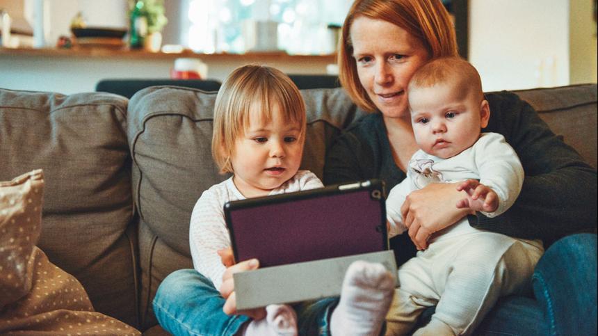 Mutter spielt zusammen mit ihrem Kleinkind und ihrem Baby mit dem Tablet