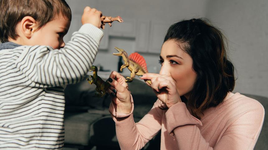 Mutter und Sohn spielen mit Dinosaurier-Spielzeug
