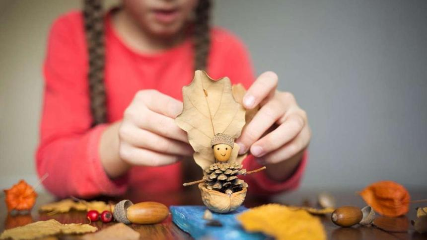 Herbstbasteln mit Kindern - Mädchen bastelt mit Eicheln und Blättern