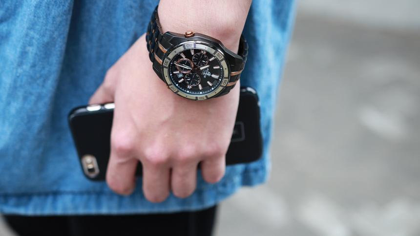 Junge mit einer Armbanduhr und einem Handy in der Haand