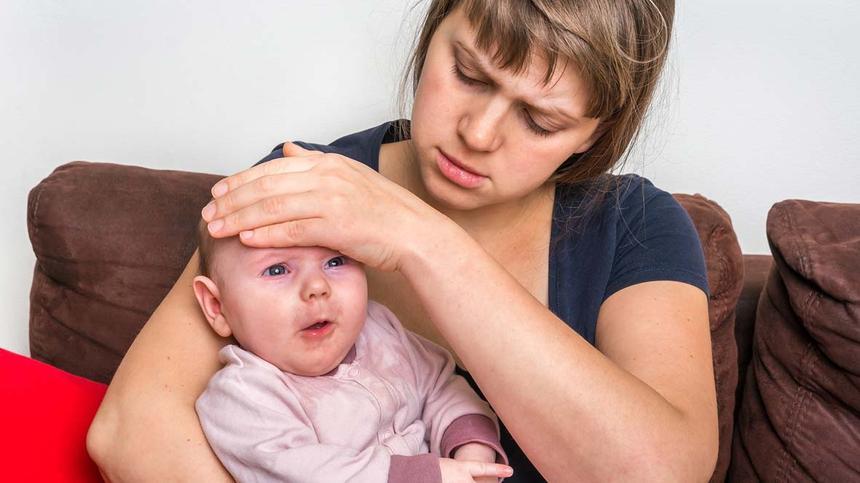 Mutter fasst ihrem Baby auf die Stirn