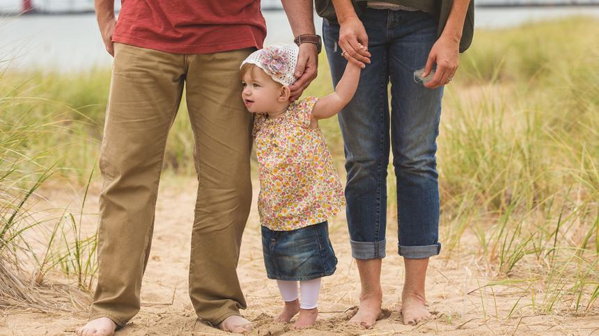 Ein Mädchen steht mit ihren Eltern auf dem Sand