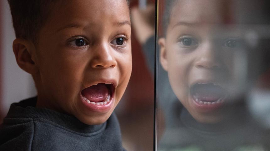 Junge hat den Mund offen - Spiegelbild im Fenster