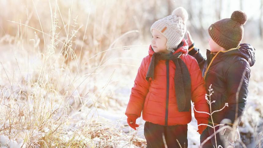 Zwei Kinder in Daunenjacken gehen im Winter spazieren