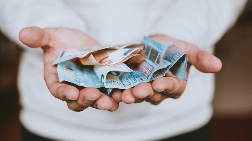 Eine Person hält Geldscheine in den Händen
