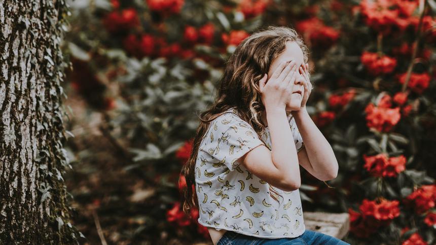 Kind sitzt mit Händen im Gesicht draußen