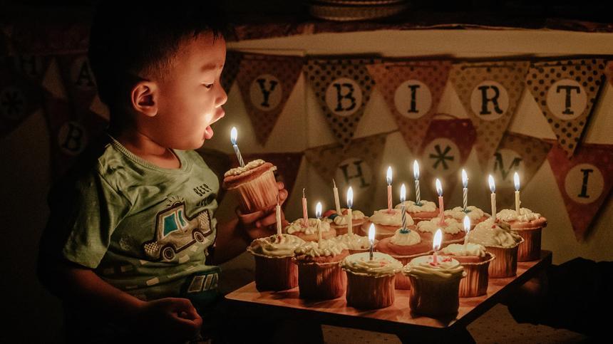 Kind bläst Kerzen auf seinem Geburtstagskuchen aus