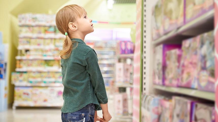 Blondes Mädchen vor einem Spielzeugregal