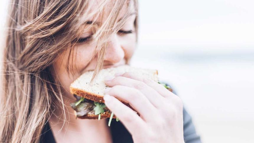 Frau isst ein Sandwhich