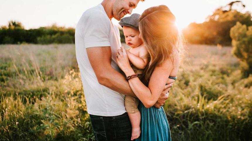 Vater und Mutter halten Baby im Arm