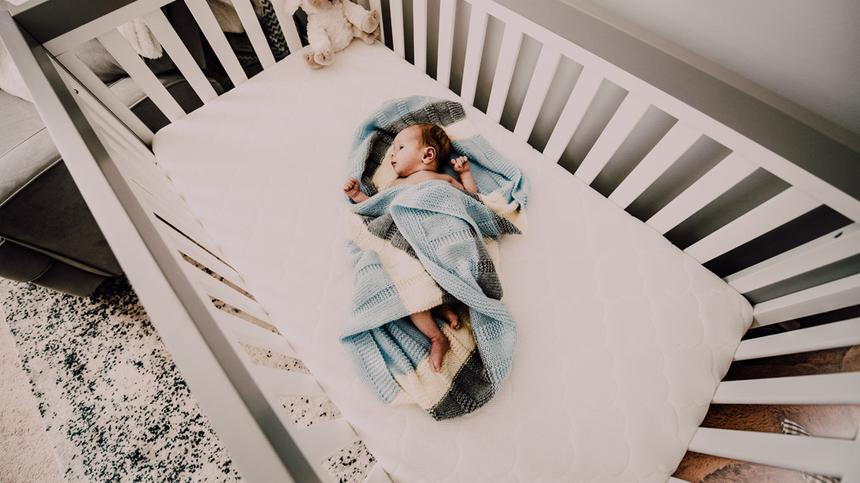 Neugeborenes liegt mit Decke umwickelt im Kinderbett