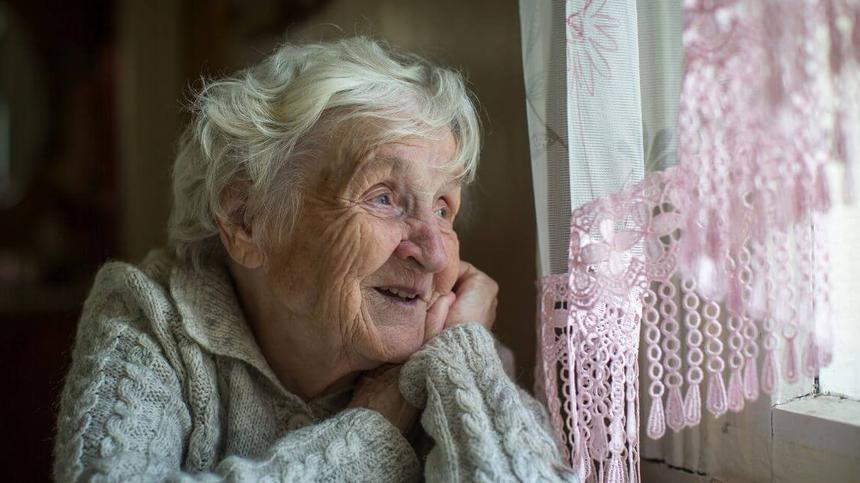Oma schaut aus Fenster