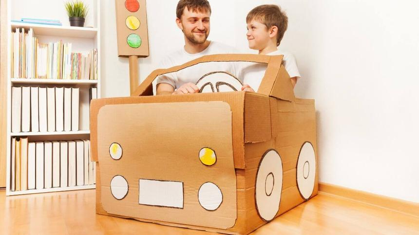 Papa sitzt mit Sohn im Auto aus Karton