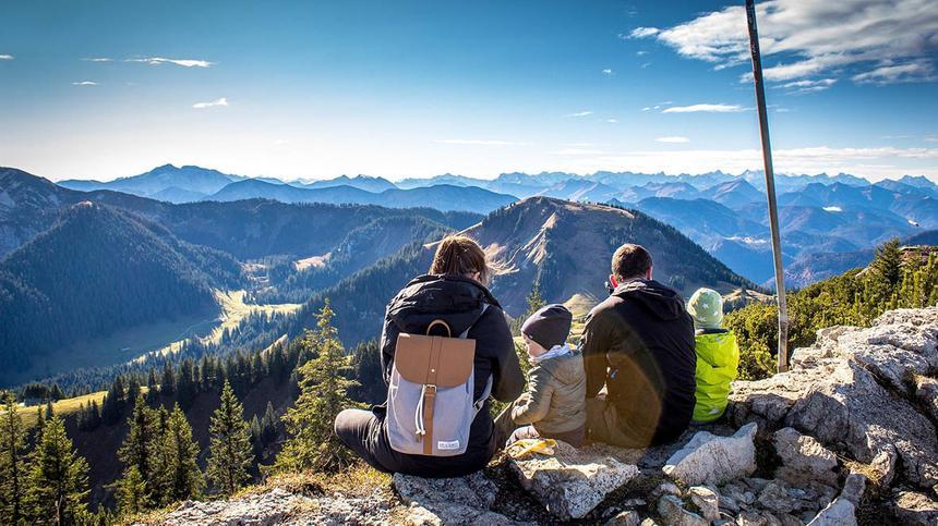 Familie sitzt auf einem Berg