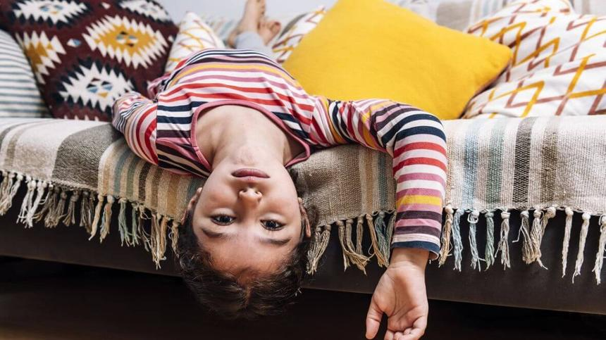 Mädchen liegt auf dem Sofa.