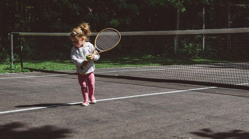 Mädchen spielt Tennis.