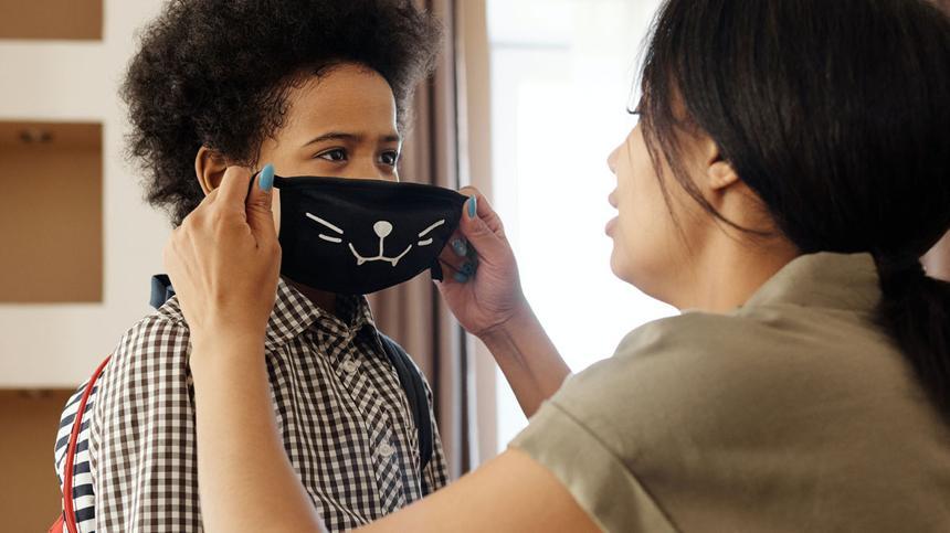 Maskenpflicht an Schulen: Mutter zieht ihrem Sohn eine Maske auf