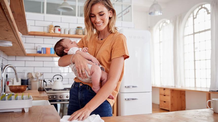 Mama mit Baby macht die Küche sauber