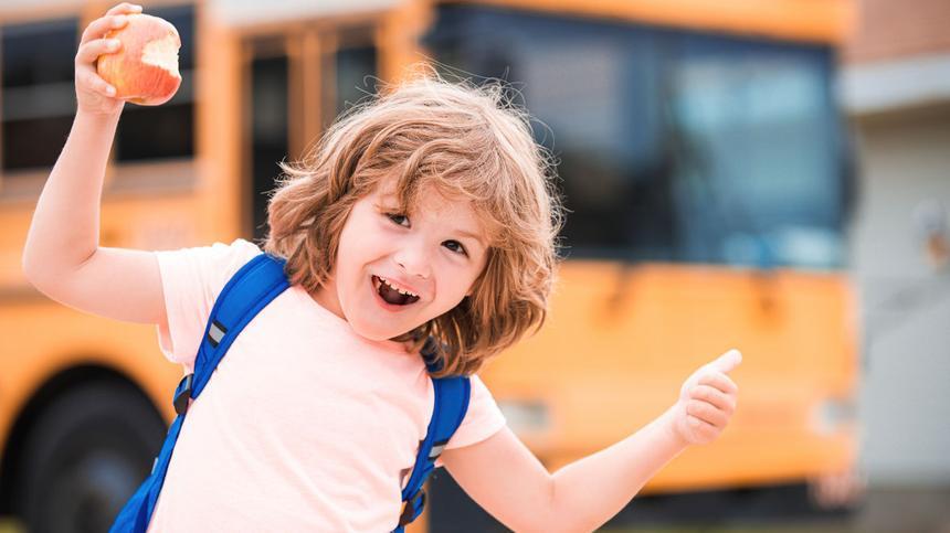 Kind vor dem Schulbus