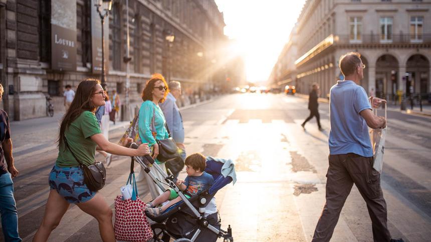 Frau schiebt einen Kinderwagen über eine Kreuzung