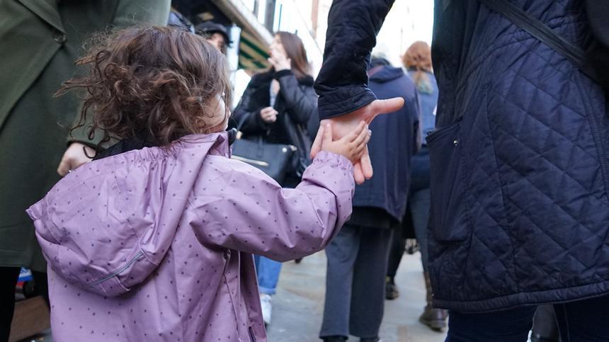 Kind hält Hand von Frau in Stadt