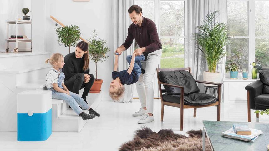 Familie sitzt im Wohnzimmer und spielt zusammen