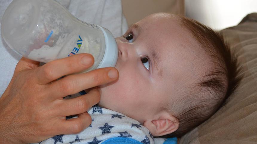 Baby trinkt aus einer Flasche
