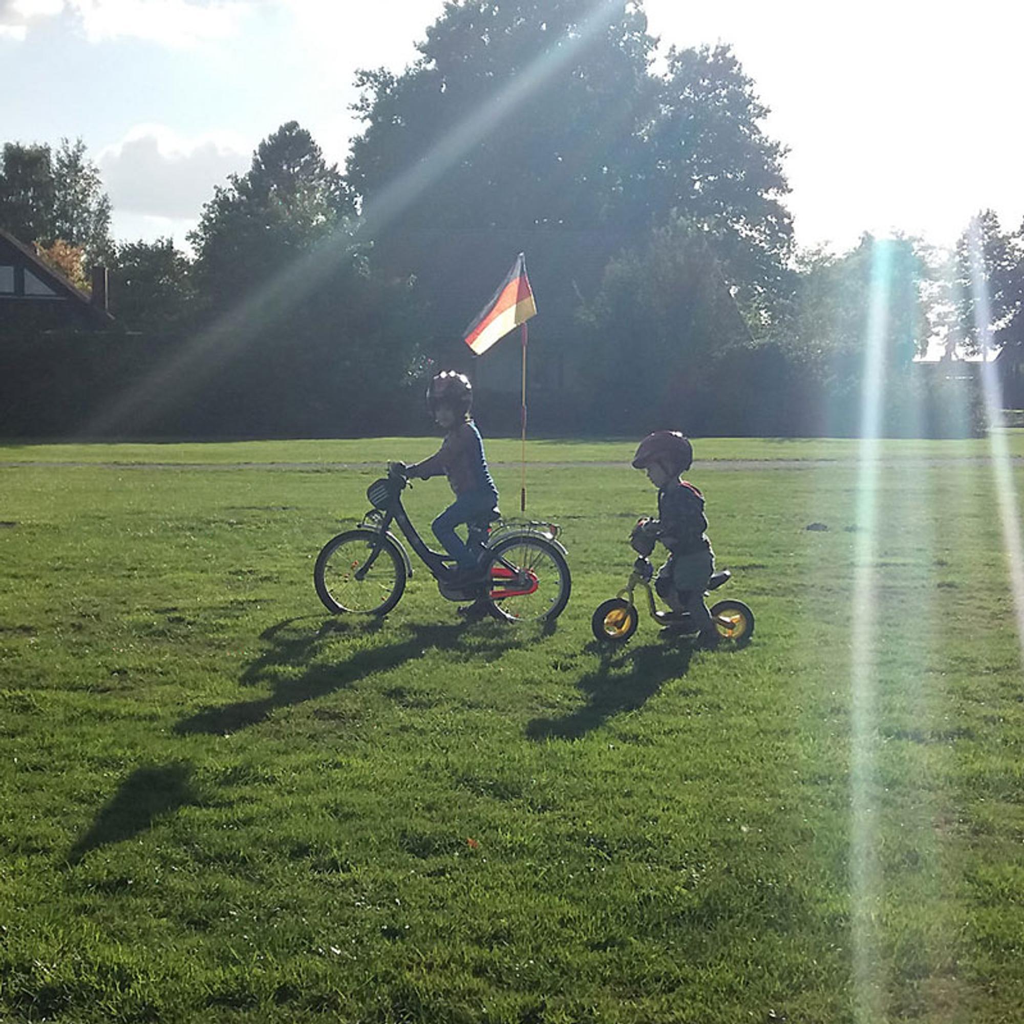 Zwei Kinder auf Wiese mit Fahrrädern