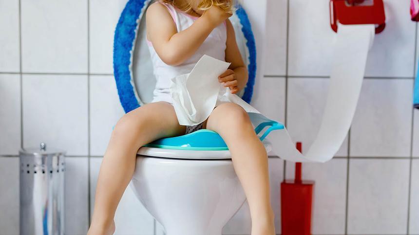 Mädchen sitzt auf einer Toilette