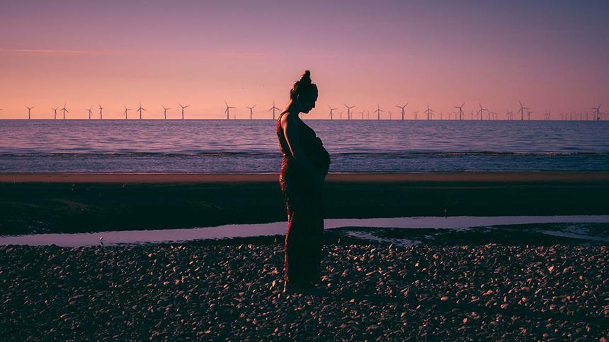 Zu wenig Fruchtwasser: Frau steht bei Sonnenuntergang am Wasser