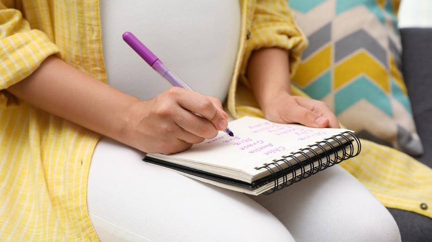 Schwangere Frau schreibt in Notizbuch