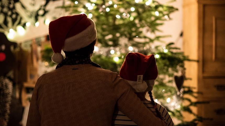 Mutter und Kind sitzen vor dem Weihnachtsbaum