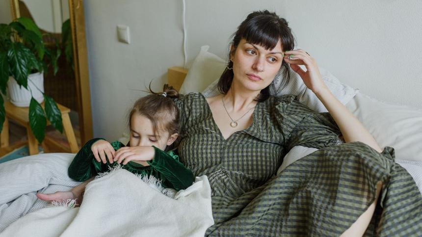 Mutter und Tochter liegen auf dem Bett