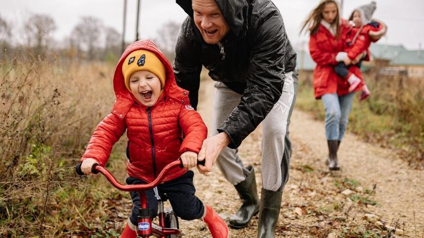Vater spielt mit Kind auf Fahrrad