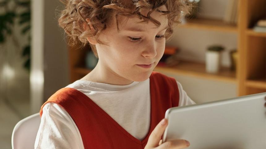 Kind hält Tablett für Homeschooling