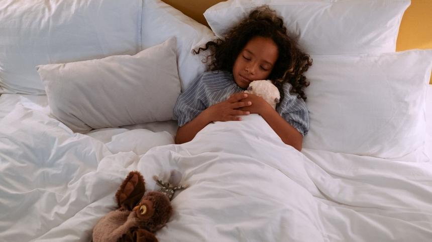 Mädchen schläft mit Kuscheltieren im Bett