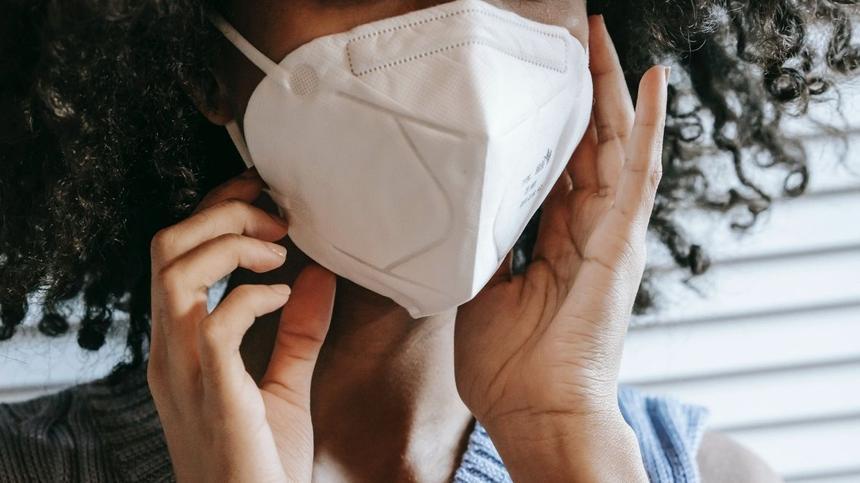 Frau trägt FFP2-Maske und berührt sie mit den Händen