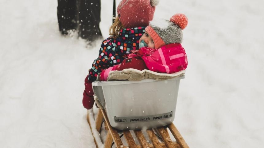 Baby in Winterkleidung wird auf Schlitten gezogen
