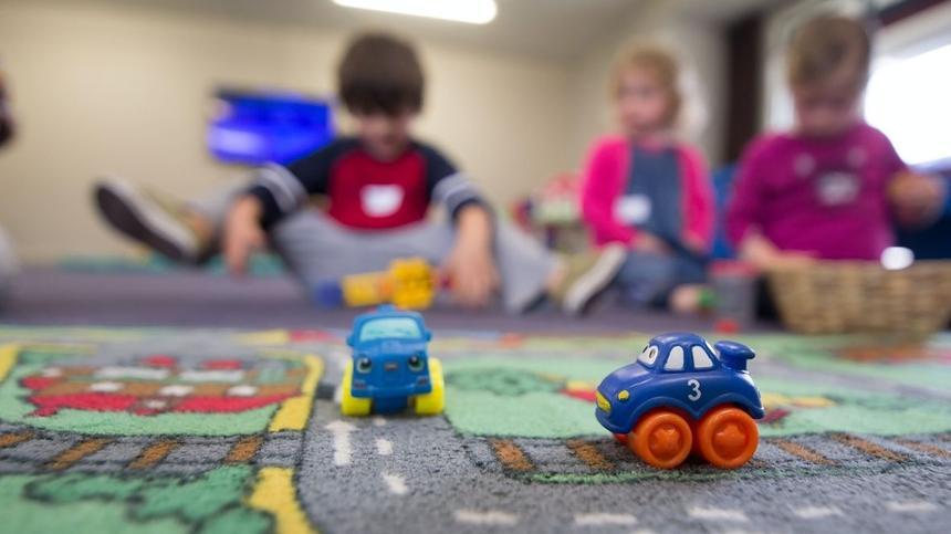 Spielzeugautos auf Teppich im Vordergrund, spielende unscharfe Kinder im Hintergrund