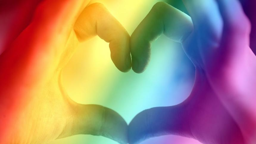 Finger bilden Herz in Regenbogenfarben