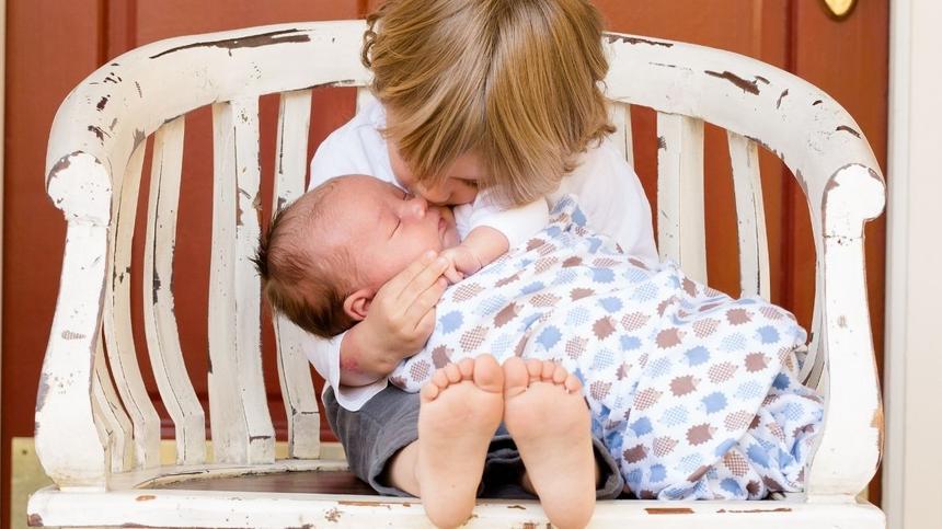 Kind hält kleines Baby im Arm